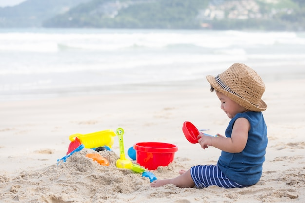 Asian baby boy playing sand on the beach