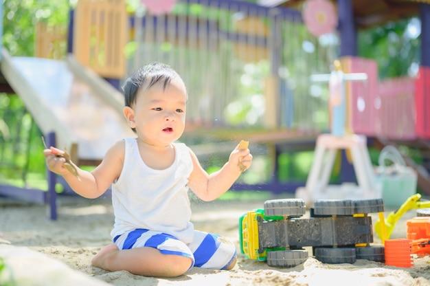 砂場で砂で遊ぶアジアの男の子。健康的なアクティブな赤ちゃんは屋外でおもちゃを再生します