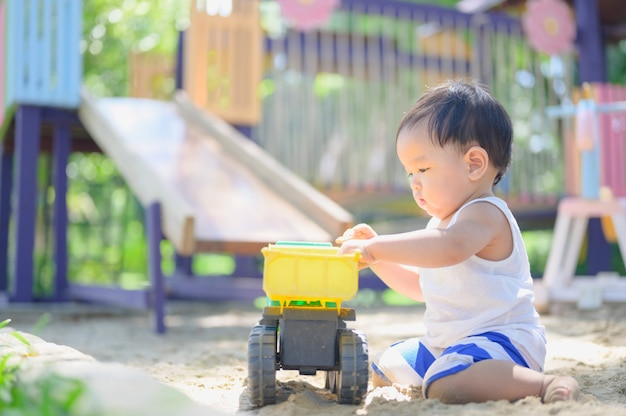 Asian baby boy playing with sand in a sandbox. healthy active baby outdoors plays toy