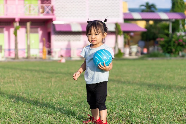 Asian baby child girl playing and​ holding a​ ball toys at the field playground.
