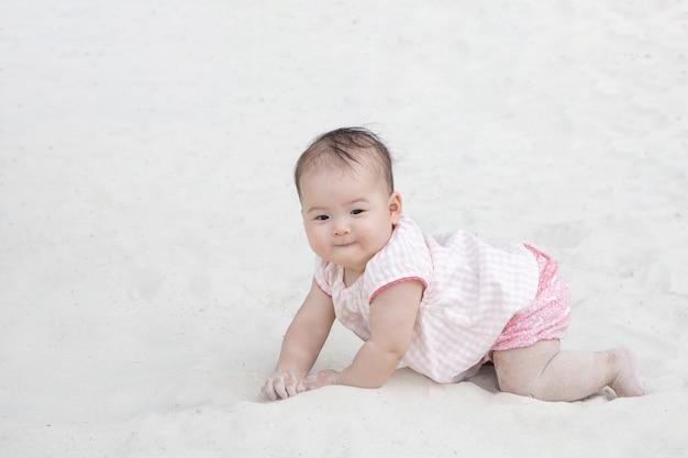 砂の上を這うアジアの赤ちゃん