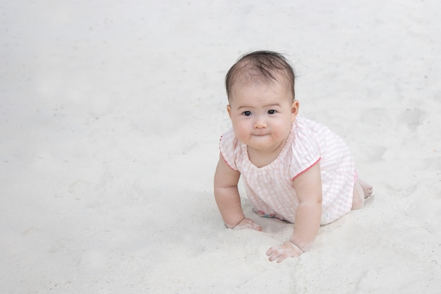 Asian baby crawling on the sand