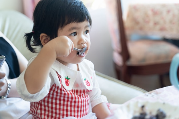 Asian baby eating chocolate cake in the cafe
