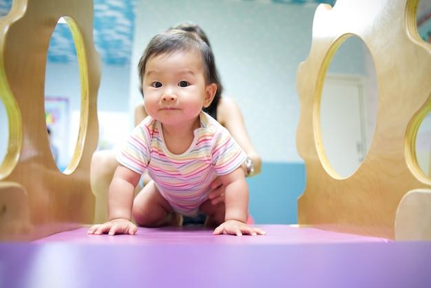 アジアの赤ちゃんは子供の遊び場で遊んで楽しむ