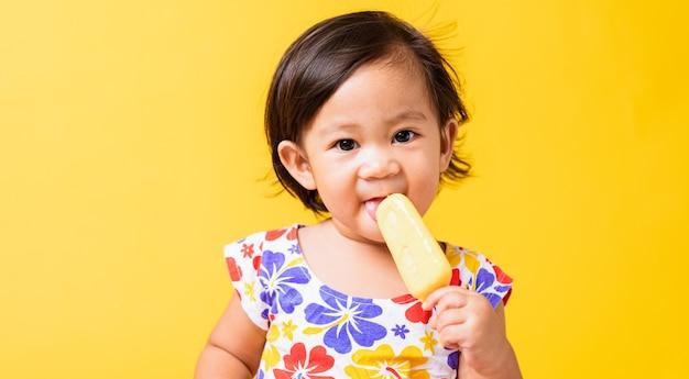 Азиатская девочка привлекательная ест мороженое