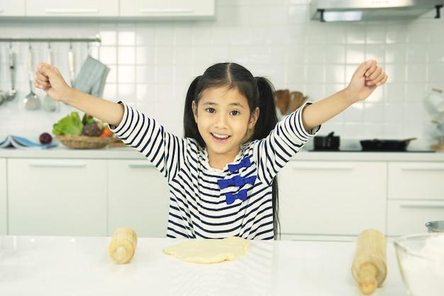 アジアの女の赤ちゃんがキッチンで準備しています。面白い小さな女の子は笑顔の歯で手を上げます。