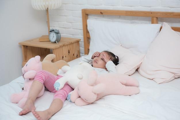 アジアの女の赤ちゃんが不幸な人形と一緒にベッドで目を覚ます。