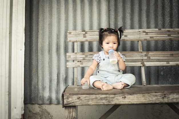 Asian baby girl with bottle of milk sitting alone on table