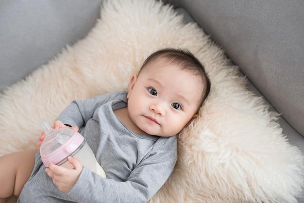 Азиатский младенец ест молоко из бутылочки через 9 месяцев после рождения