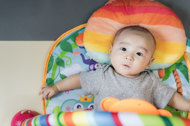 Asian baby lay down on colorful play gym. new family, protection, relaxation and relationship