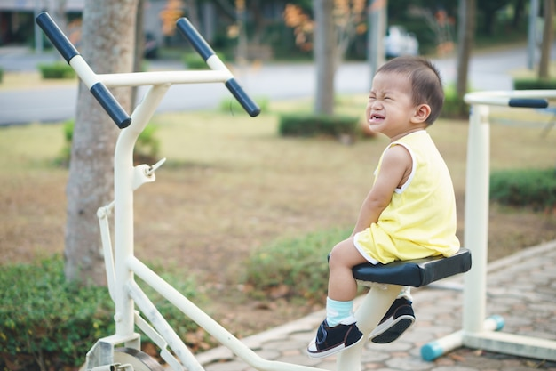 Asian baby sitting on the exercise machine