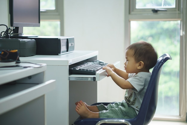 An asian baby trying to use desktop computer