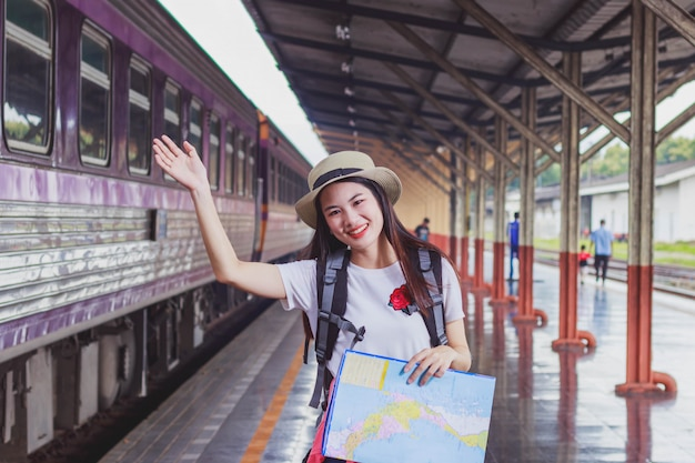 Asian backpack traveler woman holding generic local map and waving hand at train station