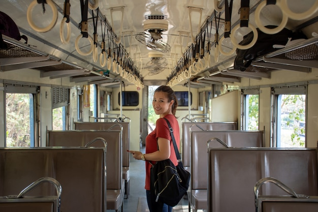 Asian backpacker inside the public train with empty seats on vacation