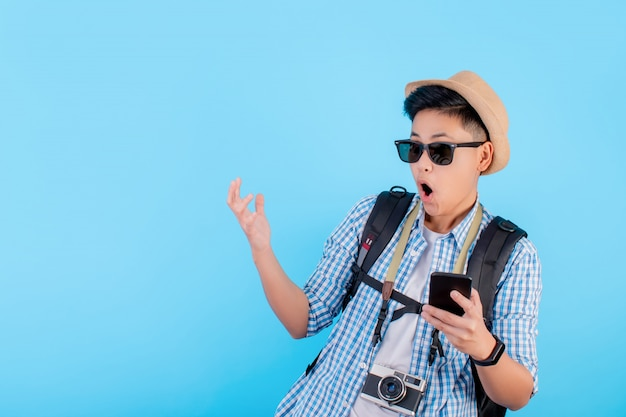 Asian backpacker traveler is shocked on a blue background