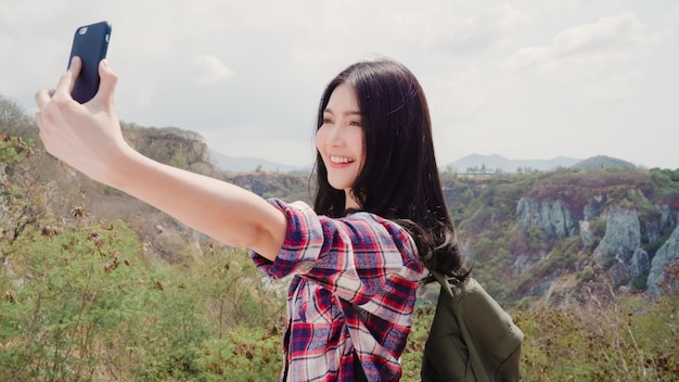 Asian backpacker woman selfie on top of mountain, young female happy using mobile phone taking selfie enjoy holidays on hiking adventure.