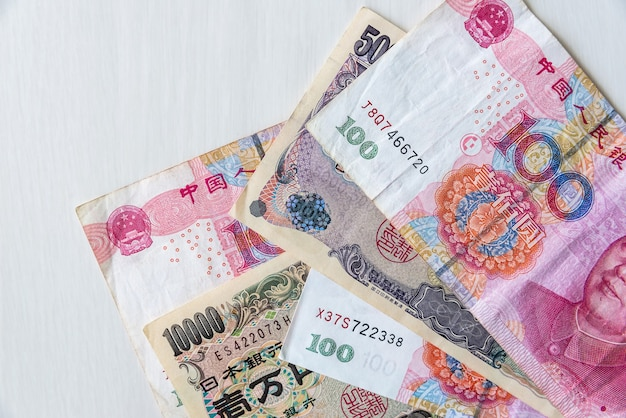 Asian banknotes, chinese and japanese on wooden background