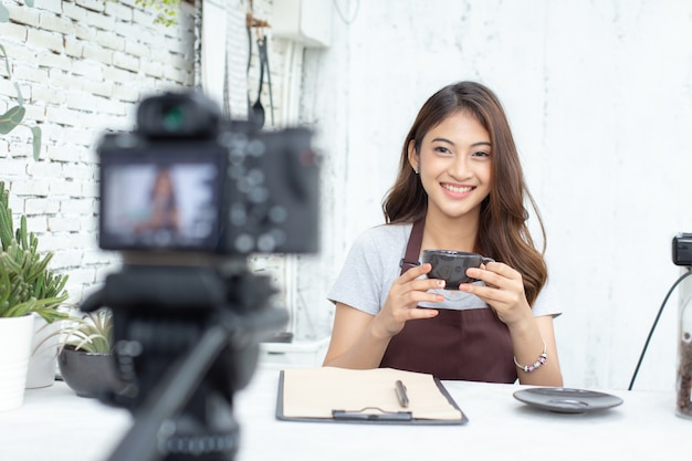 Asian barista looking to camera for live to social media