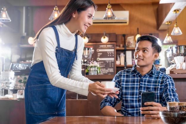 Азиатский бариста владельца малого бизнеса подает чашку кофе молодому клиенту за столом
