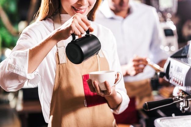 Азиатский бариста наливает молоко в чашку кофе, который представляет собой эспрессо с латте или капучино для клиента