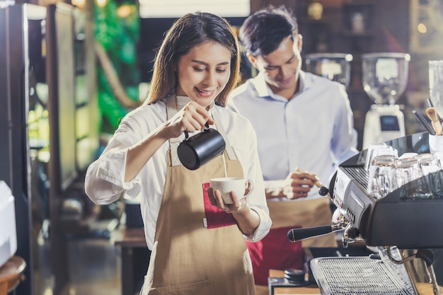 Asian barista preparing cup of coffee, espresso with latte or cappuccino for customer order in coffee shop
