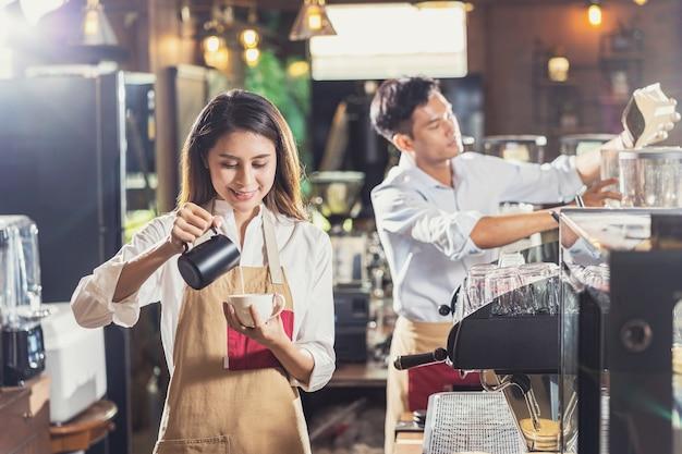 고객 주문을 위해 라떼 또는 카푸치노와 함께 커피 에스프레소 한 잔을 준비하는 아시아 바리스타