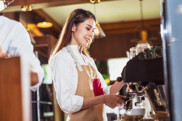 一杯のコーヒー、ラテまたはカプチーノとエスプレッソを準備するアジアのバリスタ