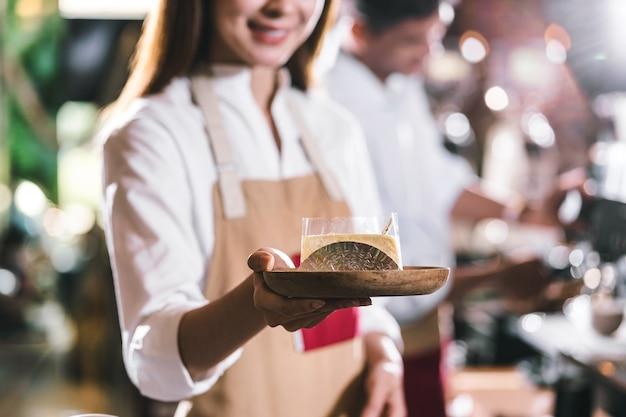 Азиатский бариста подает бумажный стаканчик кофе клиенту в кафе, владелец малого бизнеса