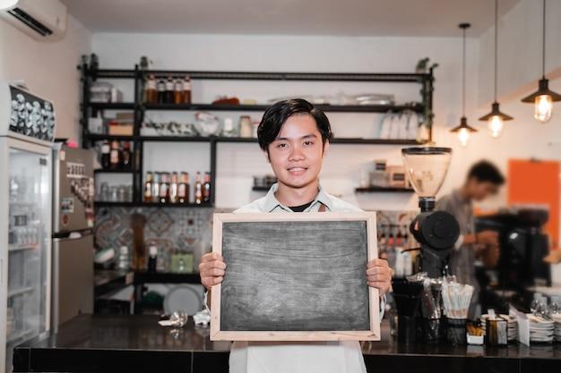 仕事が中断したときに黒板を立って保持しているアジアのバリスタ