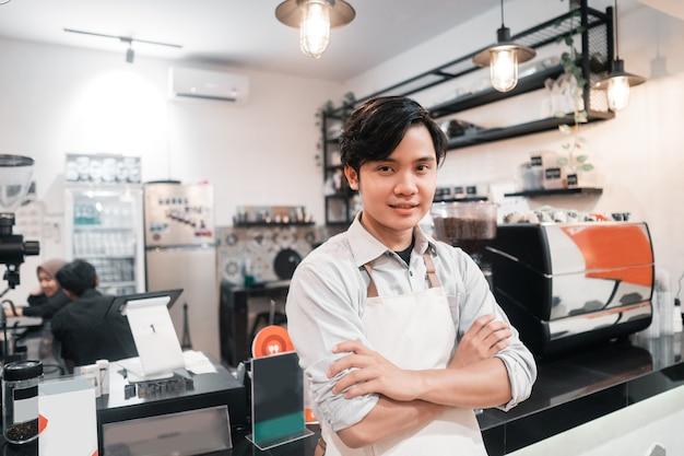 コーヒーの家で仕事が休憩するときに立っているアジアのバリスタ