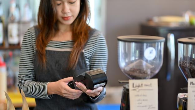 Азиатский бариста, использующий платежный терминал, вводит стоимость напитка для оплаты клиента