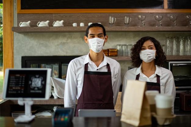 고객을 위해 종이 가방과 커피 컵을 들고 마스크를 쓴 아시아 바리스타는 레스토랑에서 입증된 코로나바이러스를 위해 가져갑니다.