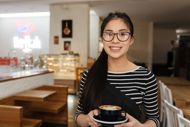 Asian barmaid with cup of coffee