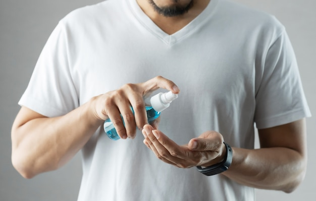Asian bearded man in white shirt standing over grey background using rubbing alcohol portable spraying on his palms and hands