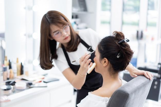 アジアの美容師がお客様のために化粧をしています。