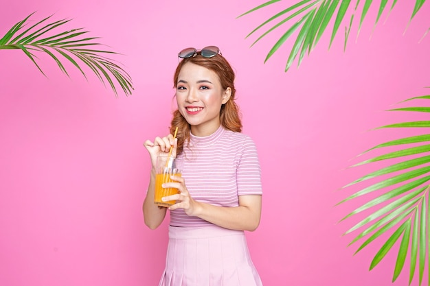 オレンジジュースとヤシの葉と夏のコンセプトのアジアの美しい魅力的なかわいい若い女の子