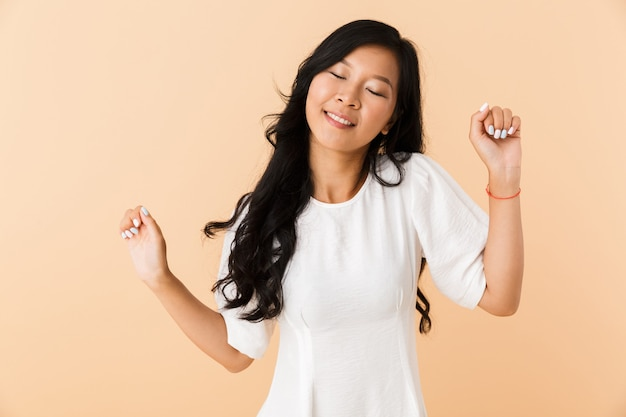 Asian beautiful attractive woman posing isolated indoors dancing.