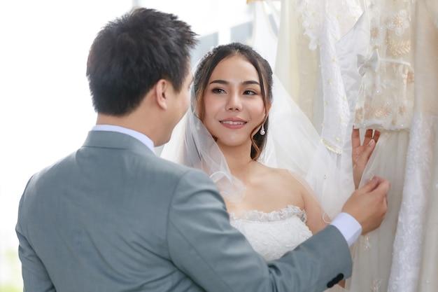 シースルーの髪のレースのベールが立っている白いウェディングドレスのアジアの美しい花嫁は、ドレッシングルームで灰色のフォーマルなスーツを着た若いハンサムな新郎と一緒に他の服を見て笑っています。