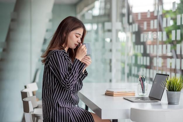 Азиатская красивая деловая женщина пьет кофе, сидя в офисе