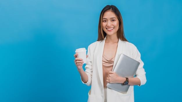 青い色の背景でラップトップとコーヒーカップを保持しているアジアの美しい実業家。
