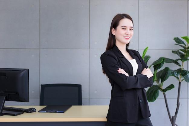 팔짱을 끼고 서서 사무실에서 행복하게 웃고 있는 아시아의 아름다운 여성 사업가 성공