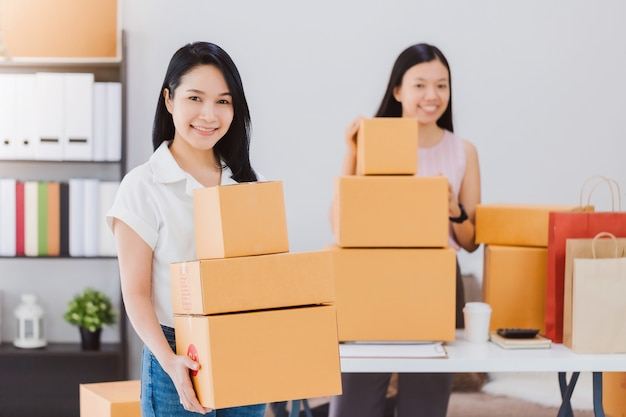 Asian beautiful empower woman and friend working with online business shop at home.owner businesswoman start up with accept orders.