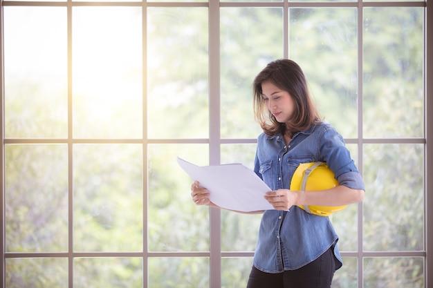 立っているブルージーンズシャツのアジアの美しい女性エンジニアと紙の計画を読み、背景にガラスフレームと黄色の安全ヘルメットを保持します。