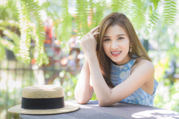 青いドレスを着たアジアの美しい女性は、良い気分で長い散歩の後に休んでいます、幸せは屋外の庭にいる間カメラを見ました。
