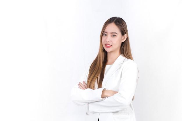 긴 금발 머리를 가진 아시아의 아름다운 여성은 흰색 양복을 입고 서서 팔짱을 끼고 있다