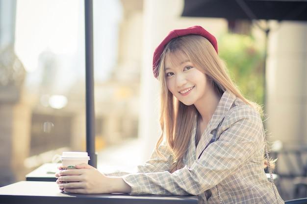 Красивая азиатская женщина в костюме и красной кепке с бронзовыми волосами сидит на стуле в кафе, в то время как солнечным утром на столе стояла кофейная кружка.