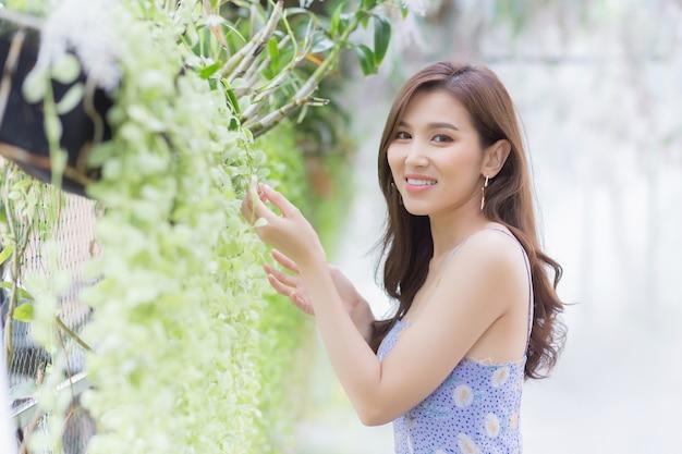 예쁜 드레스에 갈색 긴 머리를 가진 아시아 아름다운 여성은 녹색 자연 배경에 서