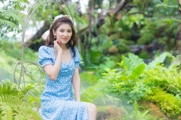 파란 드레스를 입은 아시아 아름다운 소녀가 녹색 정원 배경에 행복하게 웃고 있습니다.
