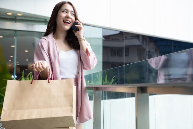 Asian beautiful girl talking on the phone with friend and holding shopping bag
