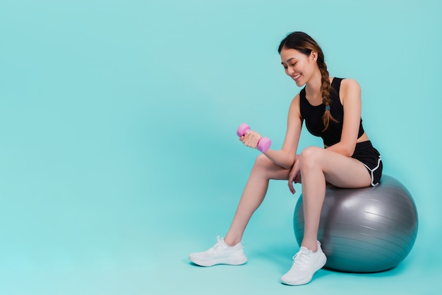 Asian beautiful happy woman holding dumbell and sitting on fit ball